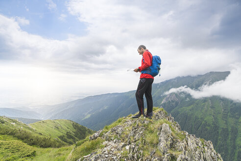 Man standing on top of a hill and checking his map in the Carpathian Mountains, Romania - SBOF01814
