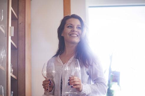 Junge Frau zu Hause mit Weingläsern - SGF02232