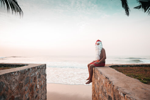Thailand, man dressed up as Santa Claus sitting on wall in front of the sea at sunset - HMEF00210