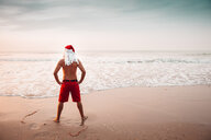 Thailand, back view of man dressed up as Santa Claus standing on the beach at sunset looking at horizon - HMEF00213
