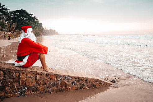 Thailand, man dressed up as Santa Claus sitting on a wall on the beach at sunset - HMEF00216
