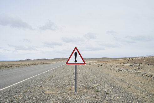 Argentina, Patagonia, Empty road with exclamation mark sign in the middle of desert - IGGF00789