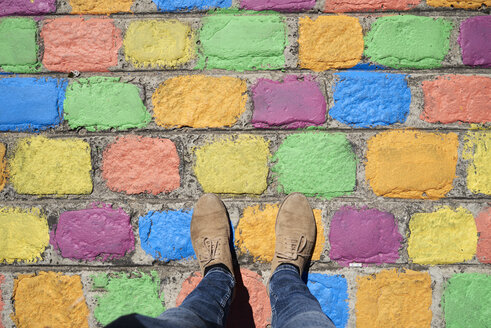 Argentina, Buenos Aires, La Boca, point of view shot of man standing on colorful pavement - IGGF00792