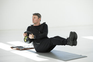 Man doing his fitness regime, doing kettle bell sit-ups - MAEF12802