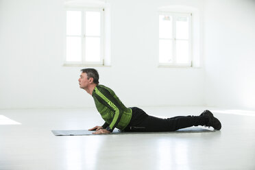 Man doing his fitness regime, practising yoga poses - MAEF12820