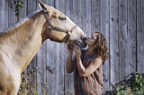 Pregnant woman stroking horse - AZF00126