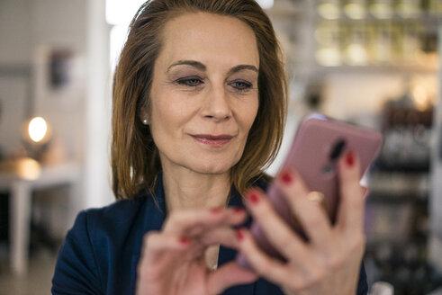 Businesswoman working in coffee shop, using smartphone - MOEF01995