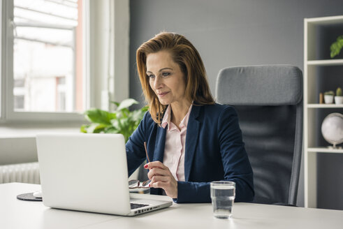 Businesswoman sitting in office, working on laptop - MOEF02049