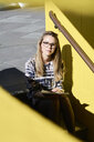 Portrait of blond student with notebook sitting on stairs outdoors - IGGF00796