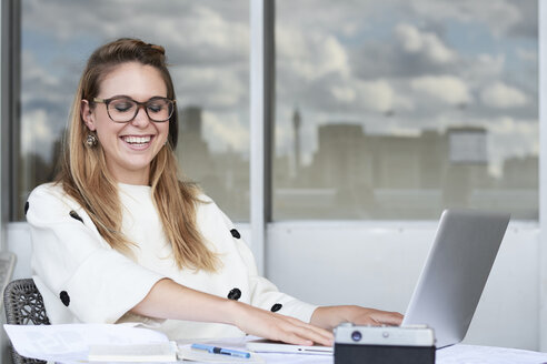 Casual businesswoman laughing while working at the office desktop with laptop. Southbank, London. - IGGF00799