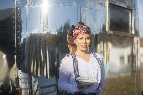 Junge Frau vor Foodtruck mit Teller - SGF02235