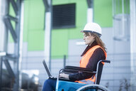 Young technician with safety helmet and vest in wheelchair working on laptop outdoors - SGF02247