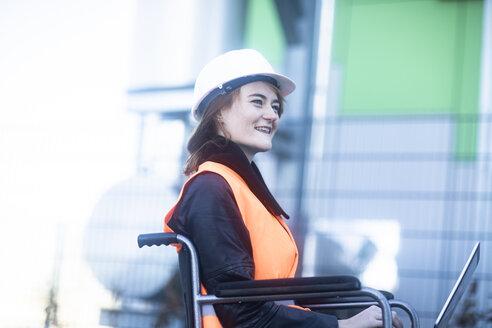 Junge Technikerin mit Helm im Rollstuhl arbeitend aussen - SGF02250