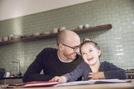 Father and daughter sitting in kitchen, doing homework - MCF00015