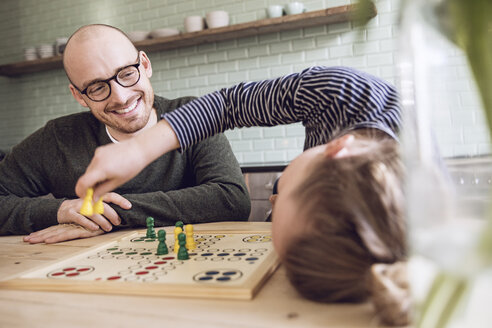 Father and daughter playing board game in the kitchen - MCF00018