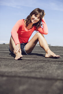 Carefree woman sitting on rooftop, sitting on rooftop - MCF00036