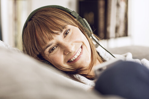 Woman lying couch, listening music with headphones - MCF00060