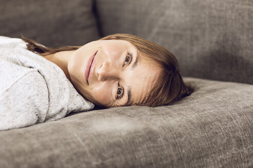 Mature woman relaxing on couch, daydreaming - MCF00063