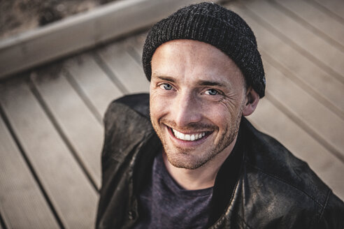 Portrait of smiling man with stubble wearing woolly hat - MCF00110