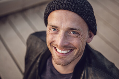 Portrait of smiling man with stubble wearing woolly hat - MCF00119