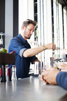 Bartender stirring whisky in glass for customers at restaurant - ASTF04033