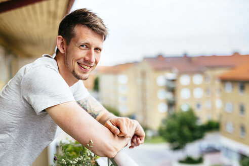 Side view portrait of happy man leaning on balcony - ASTF04081