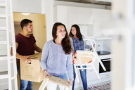 Woman with friends moving furniture in new home - ASTF04096