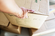 Cropped image of man's hand picking up cardboard box at new home - ASTF04099