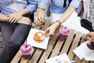 High angle view of couple having cupcake and smoothies at sidewalk cafe - ASTF04105