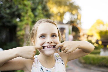 Portrait of girl pulling faces in garden - ASTF04204