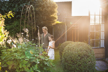 Happy mother and daughter with gardening equipment in backyard - ASTF04210