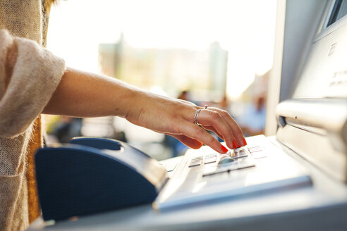 Cropped hand on woman using ticket machine at railroad station - ASTF04312
