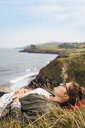 Side view of woman sleeping on grassy hill by sea - ASTF04351