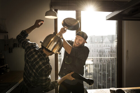 Friends having a duel with a colander and a pan in the kitchen - MJRF00002