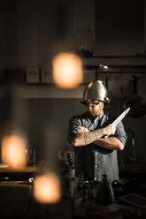 Man with kitchen knife standing in kitchen, wearing colander as helmet - MJRF00032