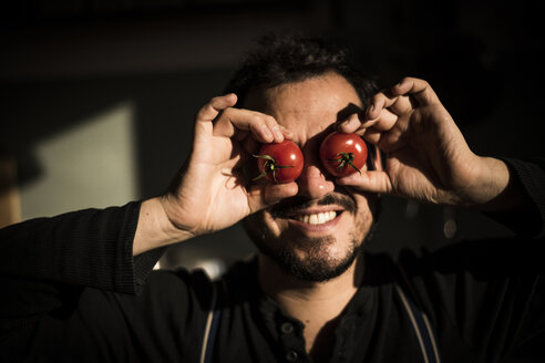 Man covering his eyes with tomatoes - MJRF00041