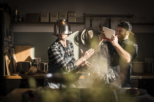 Young man filming his friend, wearing a colander as helmet in the kitchen - MJRF00044