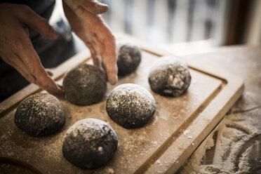Man preparing black burger buns in kitchen, letting dough rise - MJRF00050