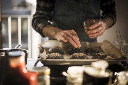 Man sprinkling sesame on burger buns on a baking tray - MJRF00056