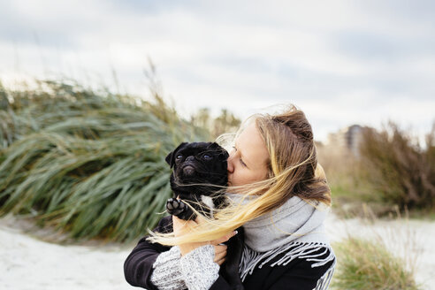 Young woman kissing dog on beach against sky - ASTF04454