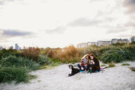 Friends sitting with dogs on beach during sunrise - ASTF04463