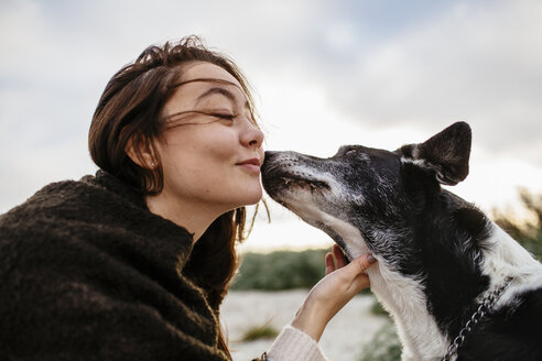 Dog kissing young woman on cheek at beach during sunrise - ASTF04469