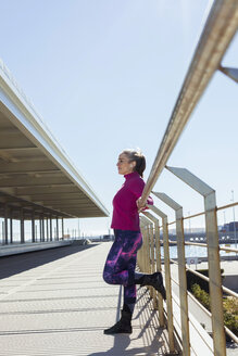 Valencia, comunidad valenciana, spain. Woman stretching after workout outside by the port. - GRSF00085