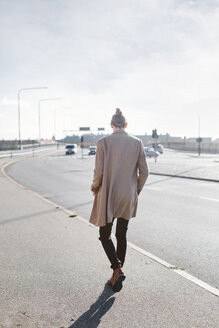 Full length rear view of young businessman walking on sidewalk - ASTF04567
