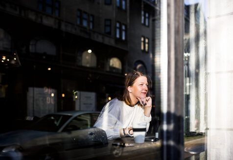 Smiling woman looking through window while sitting in cafe - ASTF04576