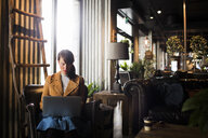 Woman using laptop while sitting in cafe - ASTF04582