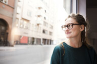 Smiling businesswoman wearing glasses while looking through office window - ASTF04597