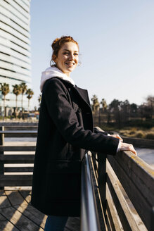 Portrait of smiling young woman leaning against a fence - JRFF02681