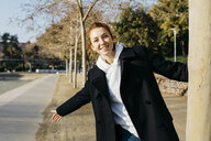 Portrait of happy redheaded young woman in a city park - JRFF02687