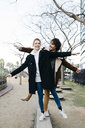 Happy couple balancing in a city park - JRFF02696